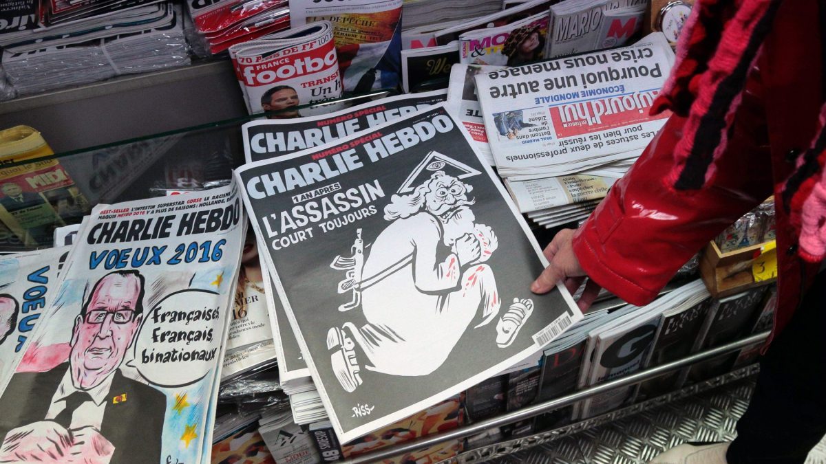 "LKS 20160106 Sig202; A woman looks at the special commemorative edition of French satirical newspaper Charlie Hebdo at a newsstand in Paris, on January 6, 2015, to mark the one-year anniversary of the jihadist attack that claimed the lives of 12 people, including three of its best-known cartoonists. True to form, the cover is unabashedly provocative, featuring a Kalashnikov-toting God figure wearing a blood-stained white robe, under the headline: ""One year on: The killer is still at large."" / AFP / JACQUES DEMARTHON - LEHTIKUVA / AFP"