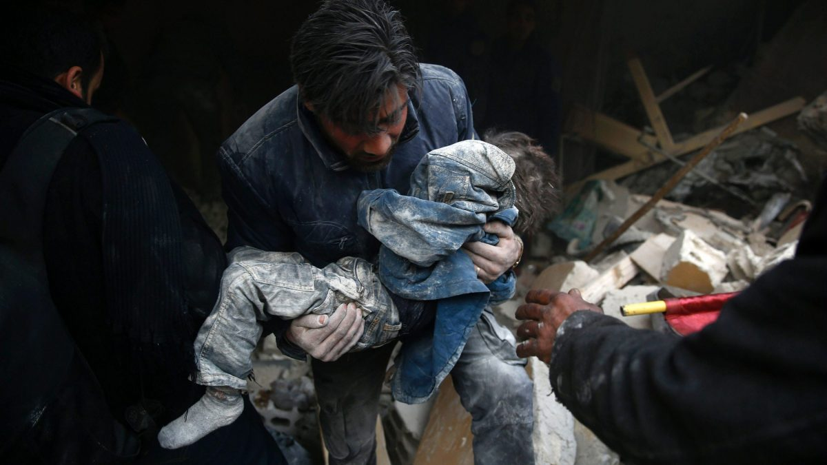 LKS 20160111  TOPSHOT - A Syrian man evacuates a child from the rubble of a destroyed building following air strikes on the Eastern Ghouta town of Douma, a rebel stronghold east of the capital Damascus, on January 10, 2016. / AFP / SAMEER AL-DOUMY - LEHTIKUVA / AFP