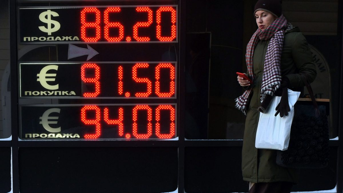 LKS 20160121 MAX1790; A woman walks past a board listing foreign currency rates against the Russian ruble in Moscow, on January 21, 2016. Russia's ruble today resumed its slide to new record lows against the dollar, tumbling over 3 percent in early trading beyond 84 to the greenback on tumbling oil prices. / AFP / VASILY MAXIMOV - LEHTIKUVA / AFP