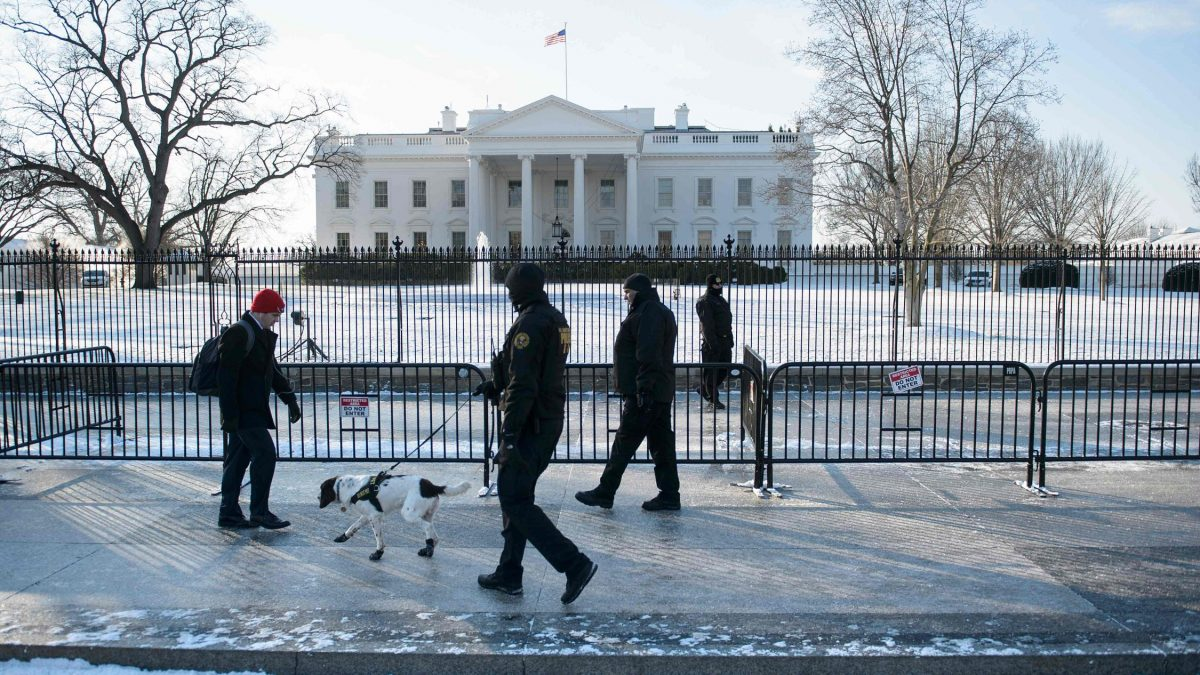 LKS 20160121 A man walks along Pennsylvania Avenue past Secret Service officers and the White House after the city received a light snow storm overnight January 21, 2016 in Washington, DC. / AFP / Brendan Smialowski - LEHTIKUVA / AFP