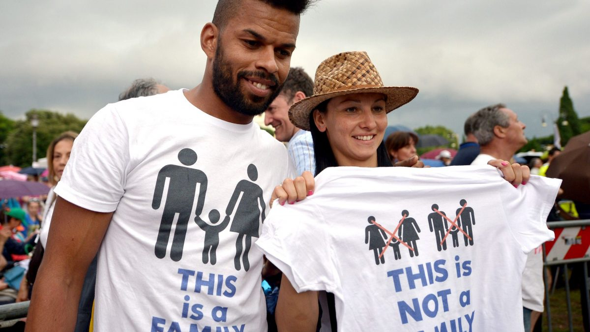 LKS 20160128 LKS 20150620 ROM2777; A couple hold-up a T-shirt with differnt family styles, during a rally in Rome's St John Square on June 20, 2015, during a demonstration against gay unions and the teaching of gender theories in schools, as Prime Minister Matteo Renzi tries to push a civil union bill through parliament. The protest comes as the Italian senate examines a civil union bill, which Renzi wants to see go to a vote in the National Assembly before the summer, with the aim of legislation being enacted by the end of the year. LEHTIKUVA / AFP PHOTO / TIZIANA FABI