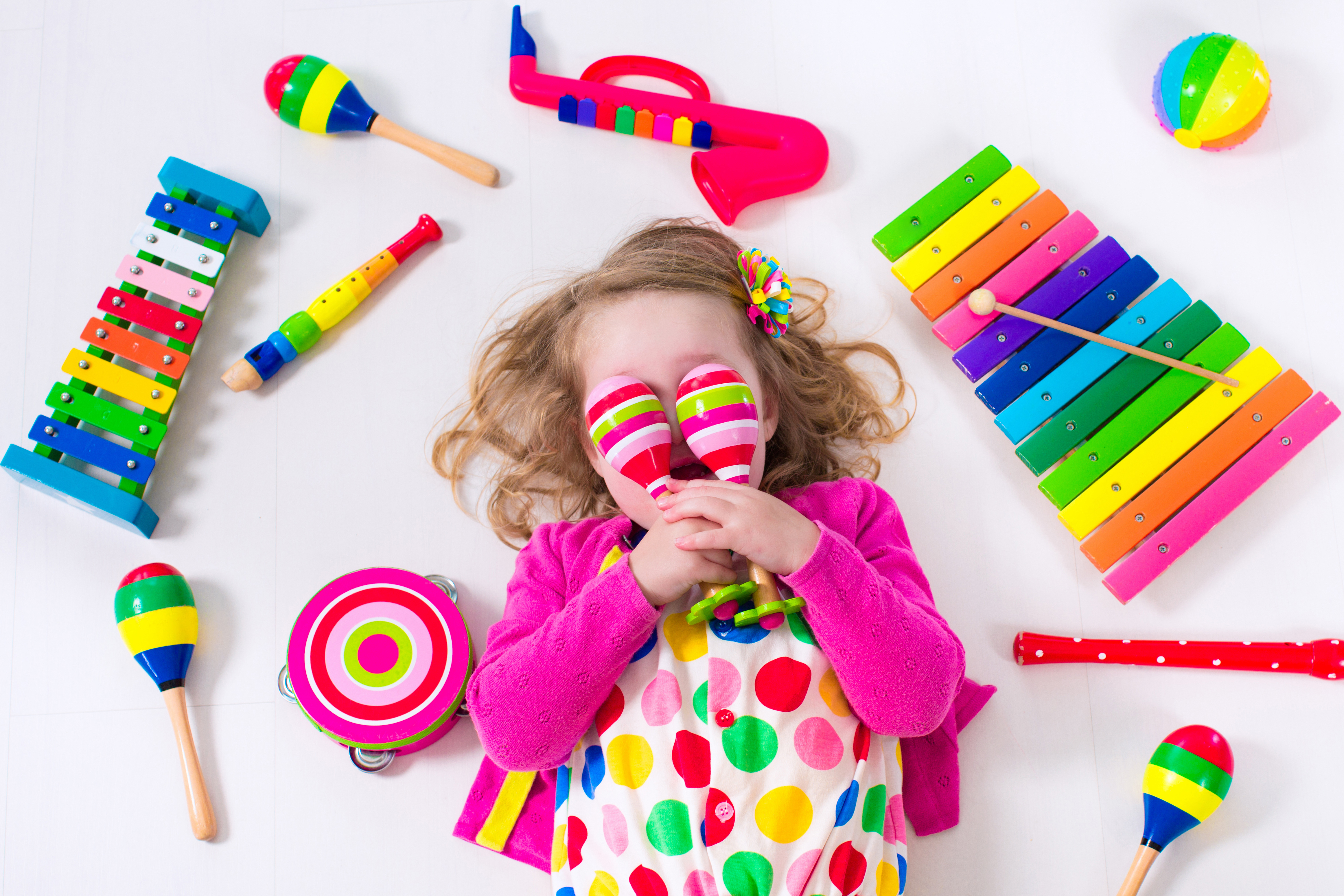 Child with music instruments. Musical education for kids. Colorful wooden art toys for kids. Little girl playing music. Kid with xylophone, guitar, flute.