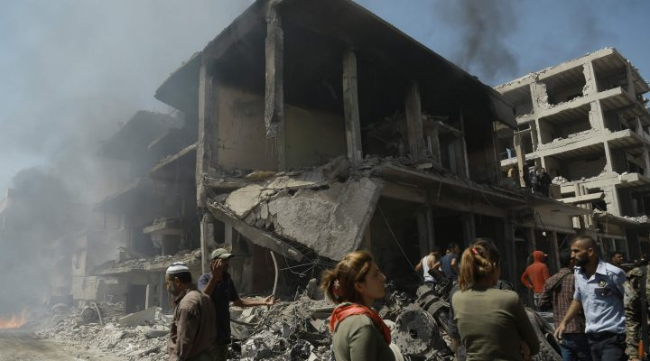 LKS 20160727 Onlookers gather at the site of a bomb attack in Syria's northeastern city of Qamishli on July 27, 2016. A double bomb attack killed at least 14 people including civilians and left dozens wounded in a Kurdish-majority city in northeast Syria, the Syrian Observatory for Human Rights said. / AFP / DELIL SOULEIMAN - LEHTIKUVA / AFP