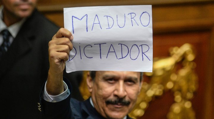 "LKS 20161024 FPZ1044; A Venezuelan opposition deputy holds up a sing reading "" Maduro dictator""  during an extraoridinary session of the National Assembly, in Caracas on October 23, 2016.  Venezuela's opposition-majority legislature declared Sunday that President Nicolas Maduro's ""regime"" committed a coup d'etat when authorities blocked a referendum on removing the unpopular leftist leader from power. / AFP / FEDERICO PARRA - LEHTIKUVA / AFP"