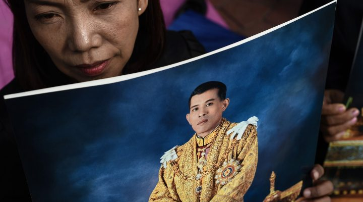 LKS 20161202 LIS1903; A woman holds an image of Thailand's new King Maha Vajiralongkorn outside the Grand Palace in Bangkok on December 2, 2016. Crown Prince Maha Vajiralongkorn became the king of Thailand late on December 1, opening a new chapter for the powerful monarchy in a country still mourning the death of his father. LEHTIKUVA / AFP PHOTO Lillian Suwanrumpha