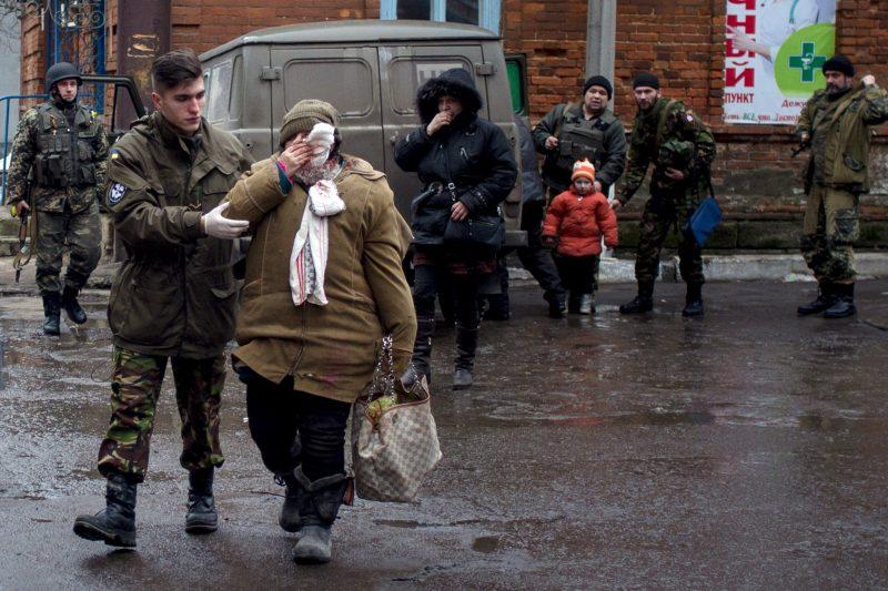 Ukrainalainen sotilas vie turvaan haavoittunutta siviiliä Donetskissa. Kaupungin tulituksessa kerrottiin useista uhreista.
